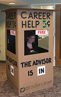 "Photo of Wright State University Career Center advisor inside the portable, cardboard box titled ""Career Help"" (5 cents crossed out, hanging sign says ""free""), ""The advisor is in."" Includes Twitter handle @raidercareer."