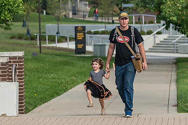 Father walking his young daughter on campus