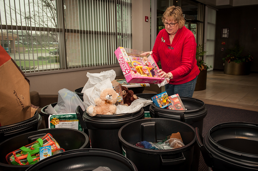 A Wright State employee places a Barbie toy into one of numerous trash cans filled with toys for needy families.