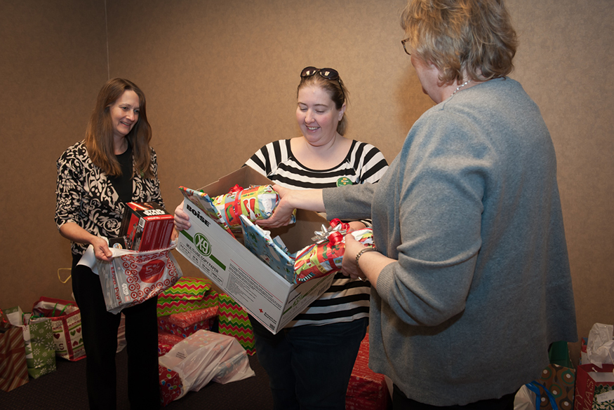 Three Wright State Employees sort wrapped gifts from a collection box for the toy drive.