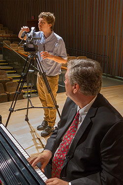 photo of a ctl staff member shooting video of a faculty member playing a piano
