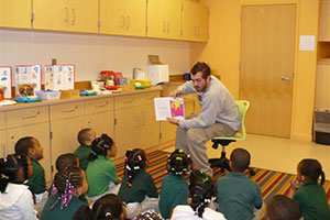 photo of a student reading to children