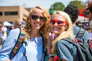 photo of two smiling students standing outside on campus