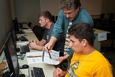 photo of a professor and two students using computers