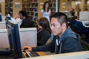 photo of a student using a computer in the library