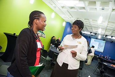 photo of a student talking to a staff member