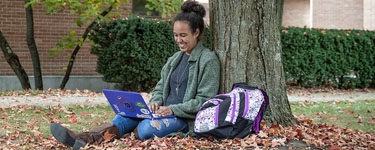 Girl sitting under a tree working on her laptop at Wright State University