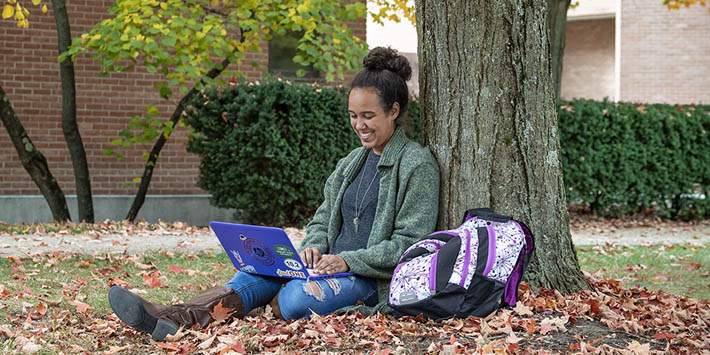 Student sitting under a tree at Wright State University studying