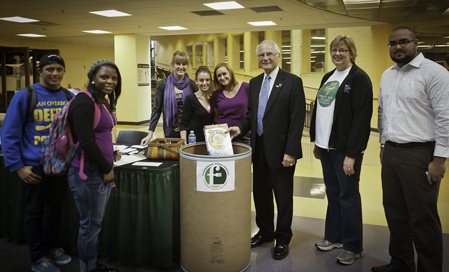 Eight people posing around collection barrel for Friendship Food Pantry