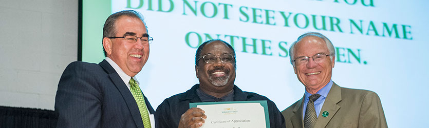 photo of a staff member receiving a certificate at the staff recognition ceremony
