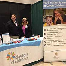 Photo from Career Fair 2018 Spring Semester, featuring two recruiters behind the Dayton Children's booth display.