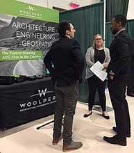 Photo from Career Fair 2018 Spring Semester, featuring a student talking to recruiters from Woolpert.
