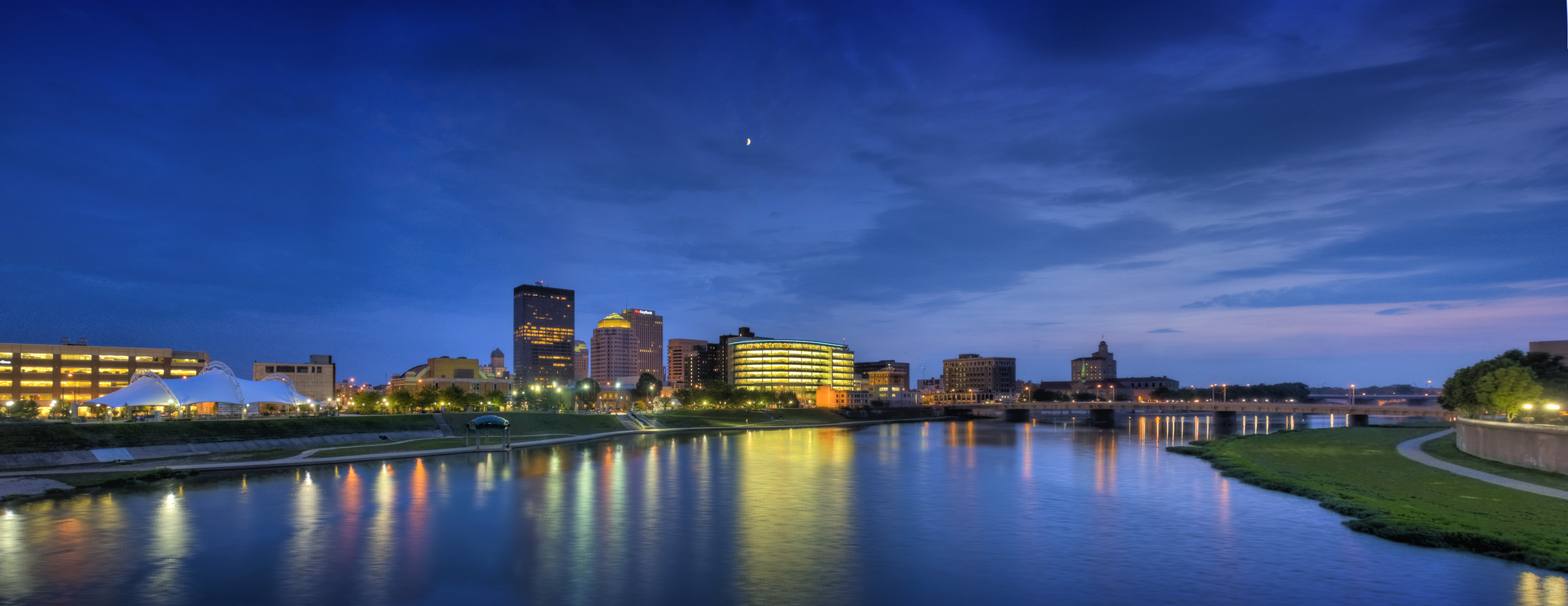 Panorama of Downtown Dayton skyline at twilight, looking across the Great Miami River near RiverScape MetroPark