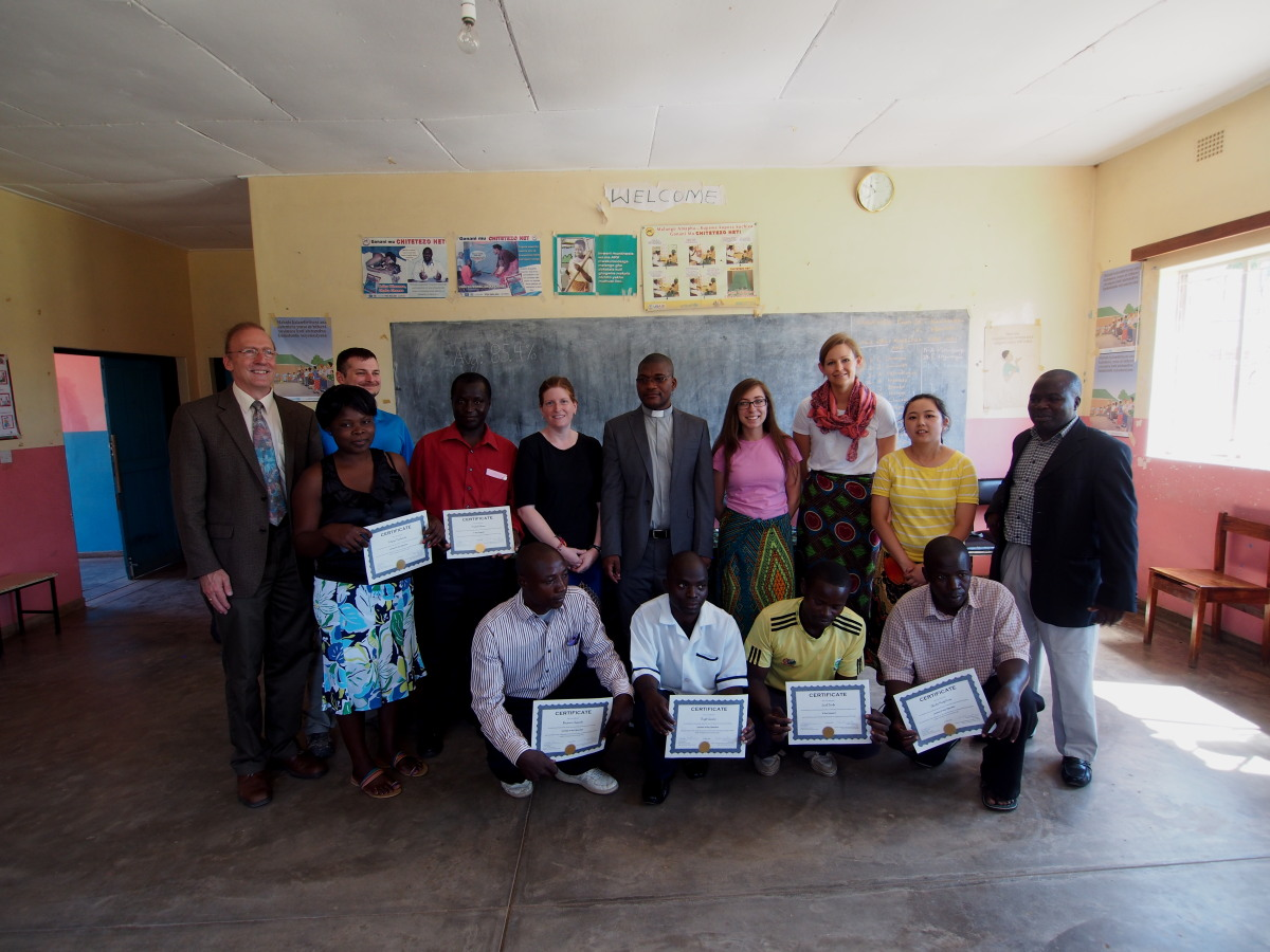 Two rows of people posing for photo: six holding certificates, eight without certificates