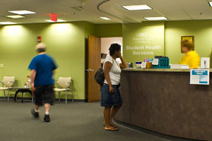photo of a student at student health services welcome desk