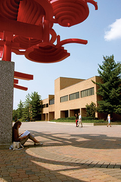 photo of a student sitting under a sculpture on campus