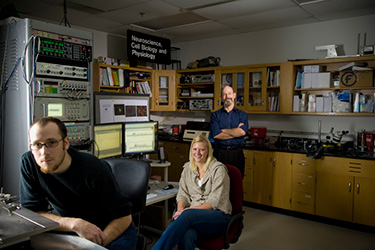 photo of a professor and students in a lab