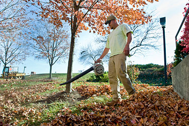 photo of a grounds employee removing leaves