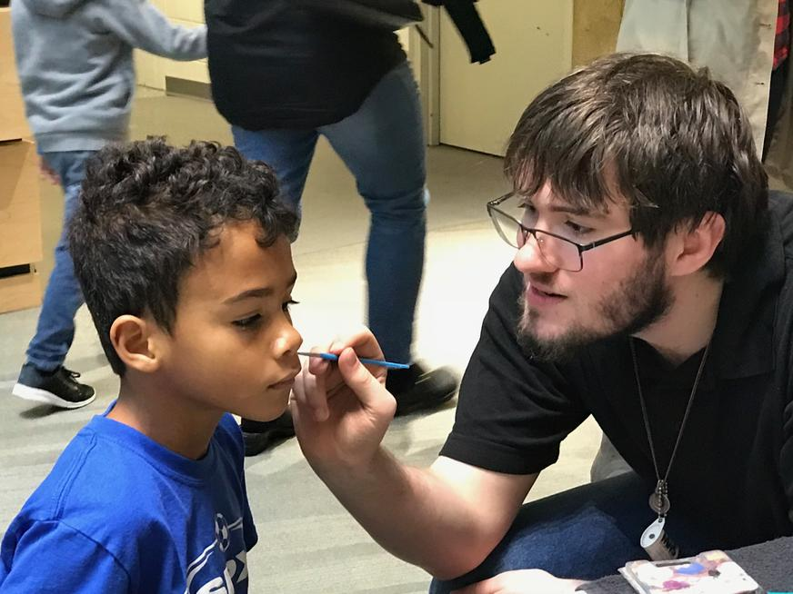 Student painting child's face