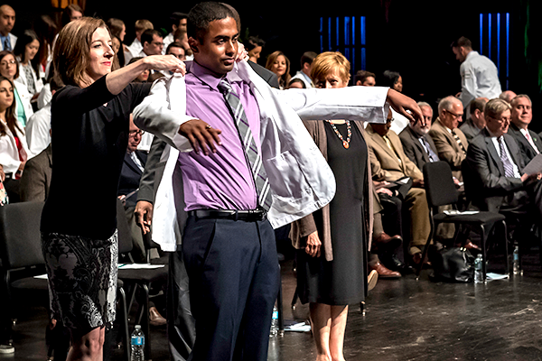 Incoming medical students receive white coats at convocation
