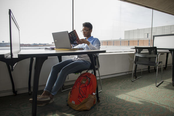 Student sits at laptop, with book