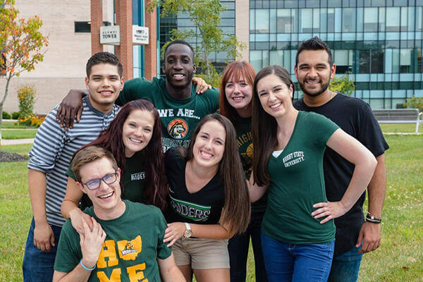 students smiling in front of the alumni tower