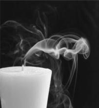 Blown out candle with smoke wisps