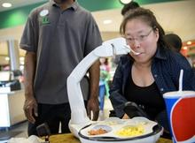 A white robotic arm brings a spoon to the mouth of a young woman.  There are a variety of foods in the 4 sections of the plate for the diner to choose from.