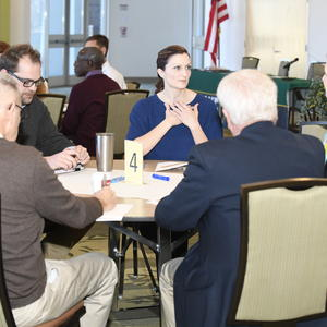 Dr. Schrader seated at table with community members.