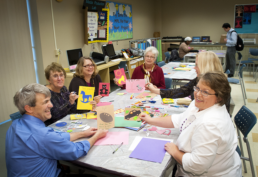 Volunteers, seated, hand-making holiday and get well cards for children in the hospital