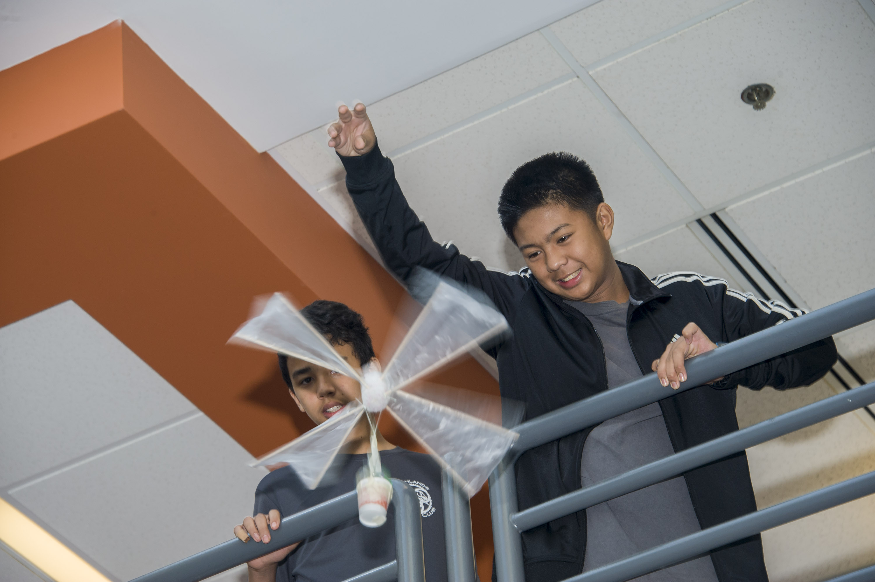 Students dropping homemade egg carriers from an elevated position