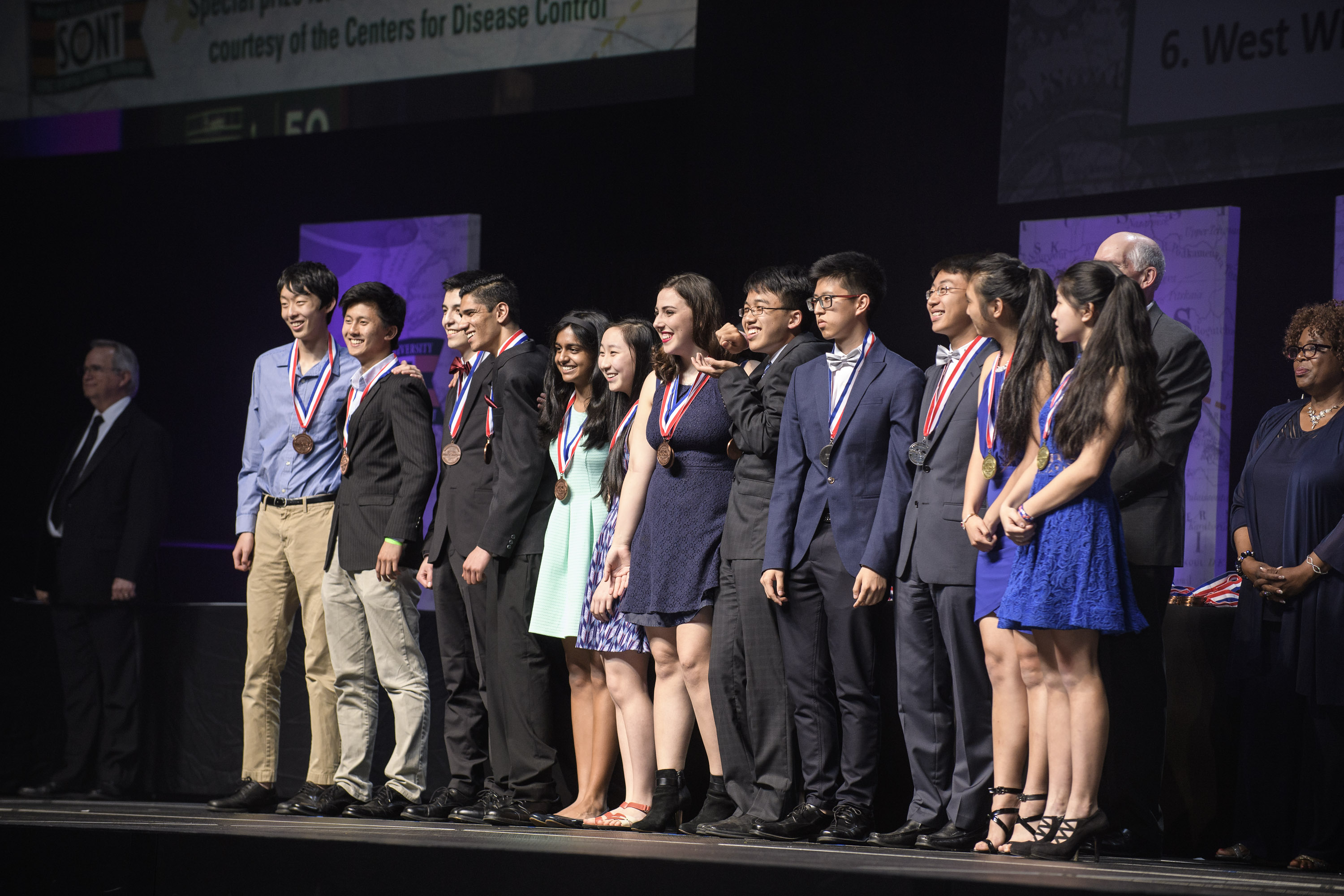 Students winning awards standing on stage