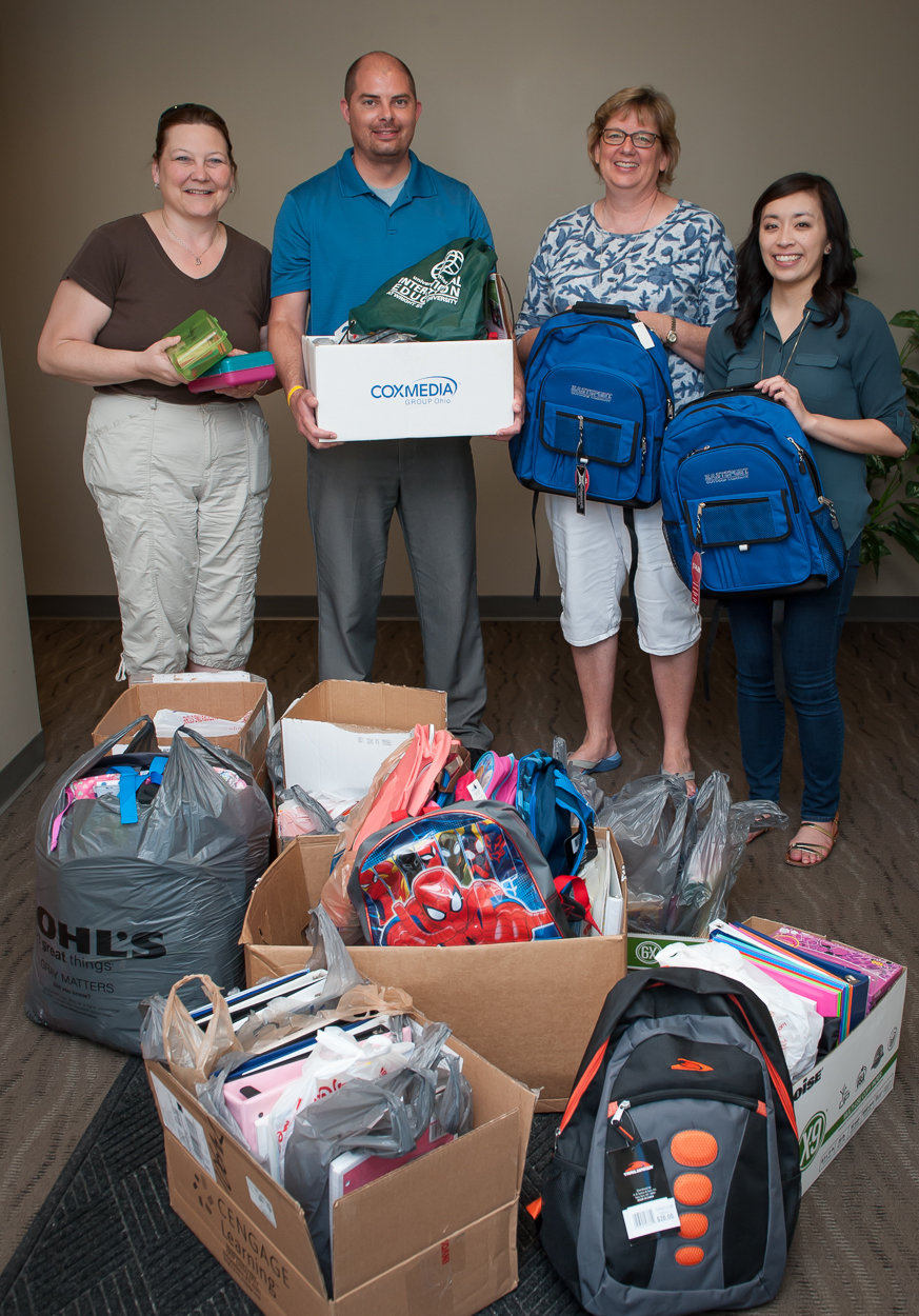 Four people standing holding backpacks and school supplies