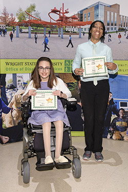 two students holding scholarship certificates at an award ceremony.