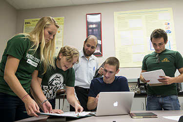 photo of students and a professor around a table