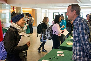 photo of a student talking to a representative at a study abroad fair
