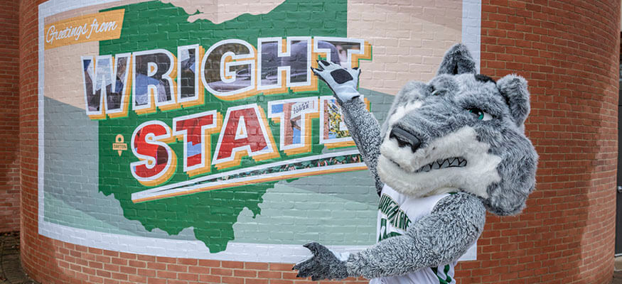 Rowdy standing infront of a wright state mural
