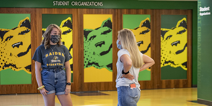 photo of two students standing and talking near student org space