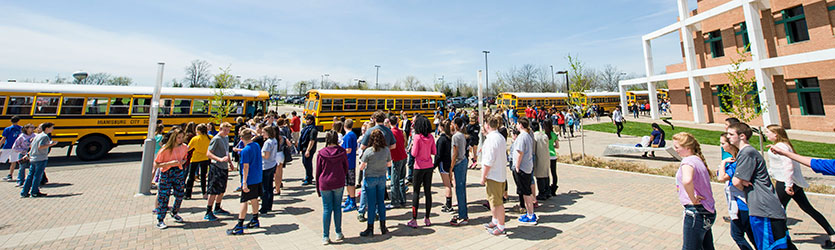 photo of children and school buses in front of the student union