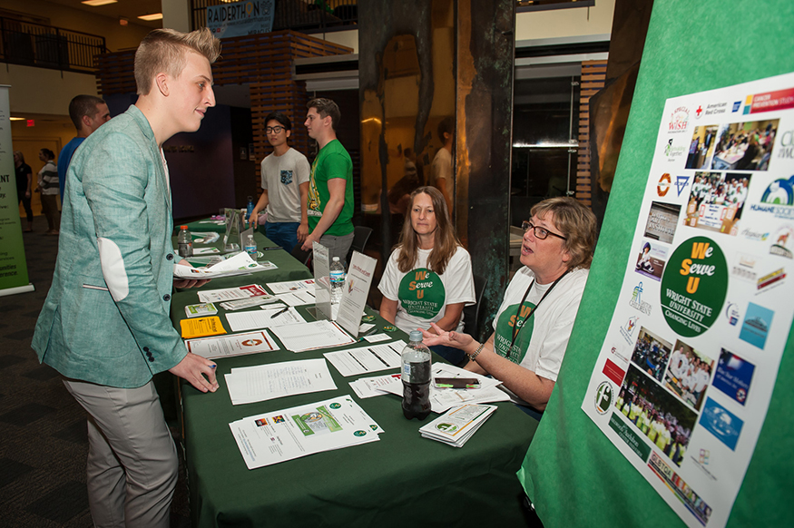 A student talks to two volunteers at an information table at the volunteer fair.