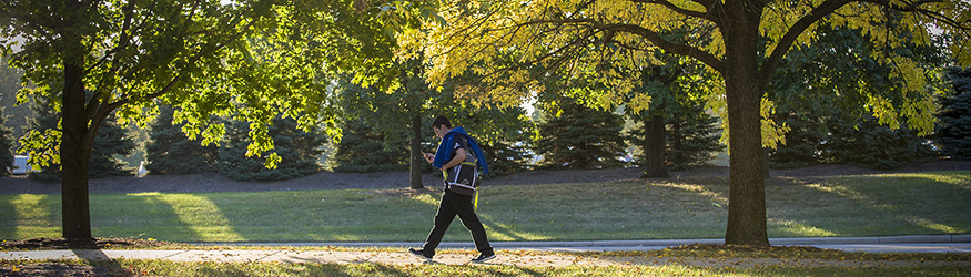 photo of a man with a phone walking on campus