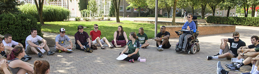photo of students sitting in a circle outside on campus