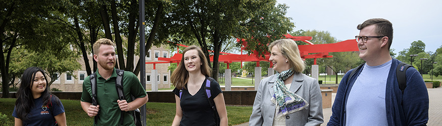 photo of president schrader and students walking on campus