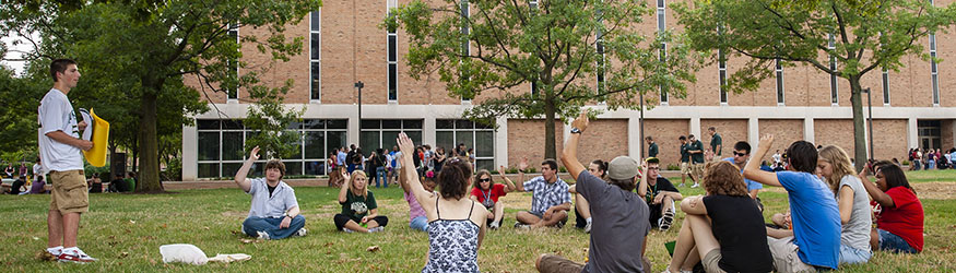 photo of students sitting in a circle outside