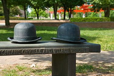 photo of bench with wright bros hats on campus