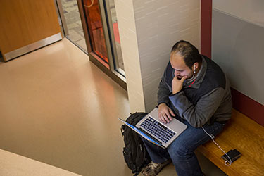 photo of a student looking at a laptop
