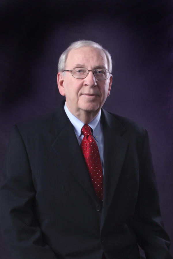 Image of Colonel David Madden in black jacket, red tie, white dress shirt, and glasses