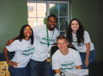 Four students stand around a table smiling, wearing Res Life t-shirts