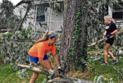 Women's soccer players cleaning up after storm